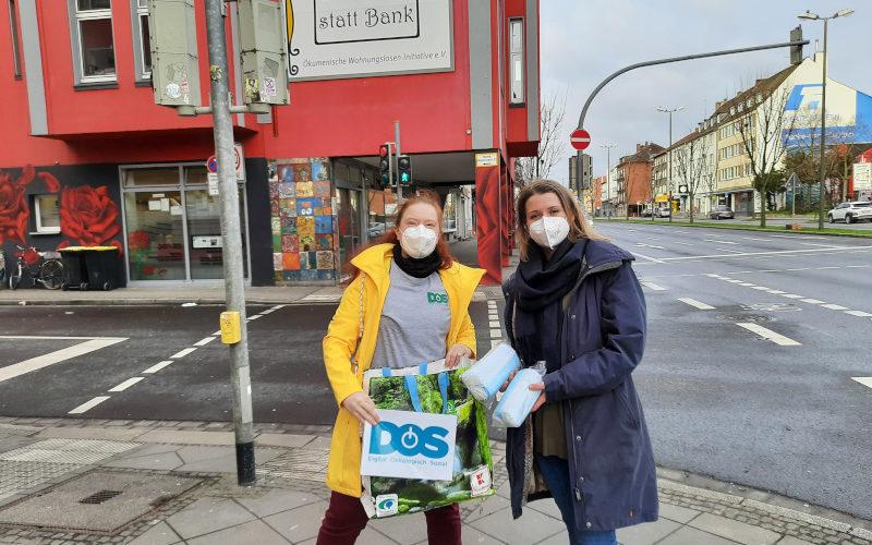 Eine Frau mit DOS-Logo in der Hand und und eine Frau mit Maskenpächkchen stehen auf der Straße. Im Hintergrund ein Gebäude auf dem ein großes Schild hängt auf dem Steht: Gast-Haus statt Bank