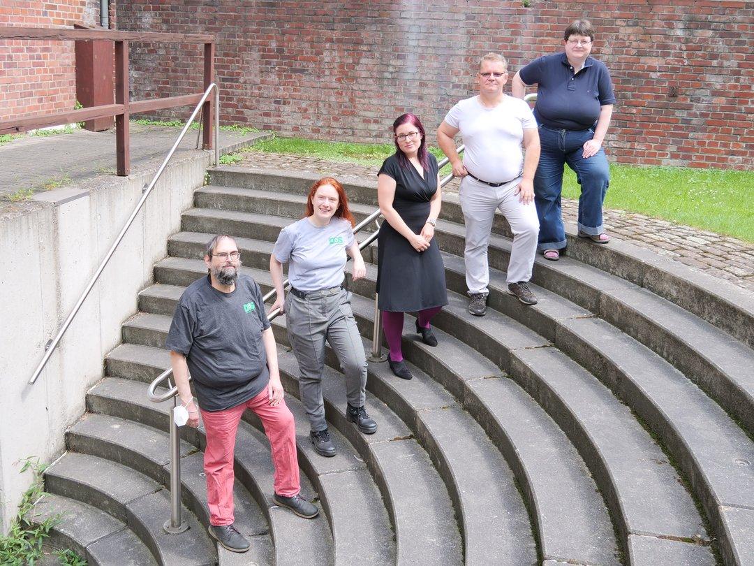 5 von 6 Vorstandsmitgliedern schräg auf einer Treppe