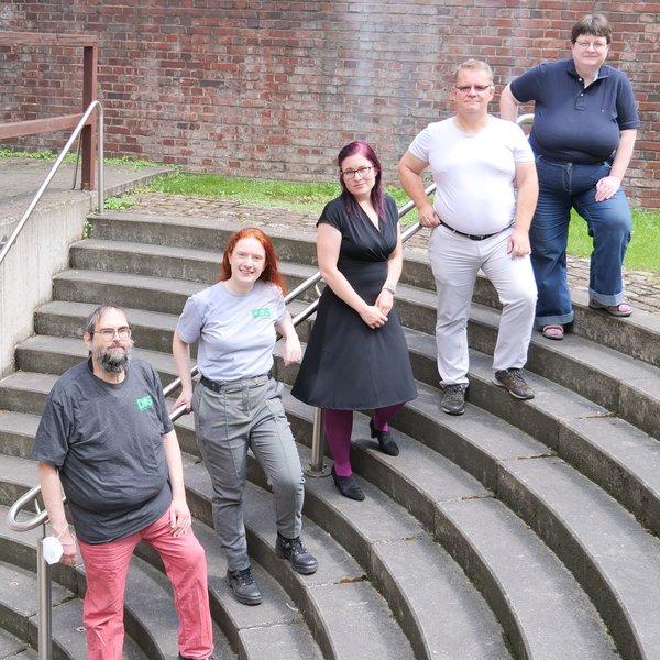 Foto von 5 Vorstandsmitgliedern. Die Vorstandsmitglieder stehen vor dem Gelender einer runden Treppe
